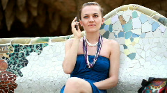 Young woman talking on cellphone, shot in Park Guell, Barcelona Stock Footage
