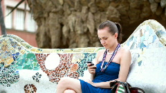 Woman sending text message, shot in Park Guell, Barcelona Stock Footage