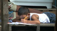 Young Asian Boy Doing Homework In The Slums Stock Footage