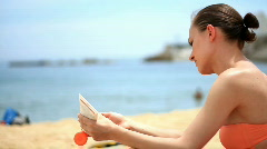 Woman on the beach applying lotion Stock Footage