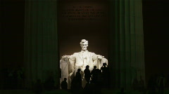 Silhouettes of people in front of statue at Lincoln Memorial illuminated at - stock footage