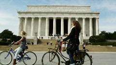 Two young women riding bikes in front of Abraham Lincoln Memorial Stock Footage