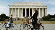 Stock Video Footage of Two young women riding bikes in front of Abraham Lincoln Memorial