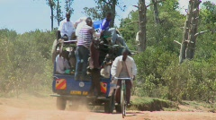 A van crowded with passengers makes its way along a dirt road in East Africa. Stock Footage