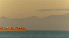 Container ship at sunset through frame Stock Footage