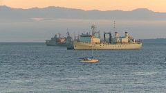 Military, navy tug passes navy ships at sunset Stock Footage