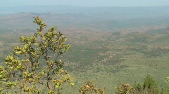 Pan across to a Masai warrior standing at the edge of a vast canyon in Northern Stock Footage