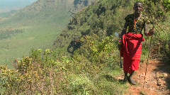 Tilt up to reveal a Masai warrior standing at the edge of a vast canyon in Stock Footage