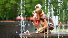 Child and mother in the fountains. Mother takes baby shoes Stock Footage