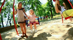 Child riding on a swing. His mother stands beside-1 - stock footage