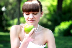 Young woman eats fresh apple outdoor Stock Footage