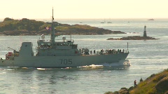 Military, navy, Coastal defense ship passes lighthouse Stock Footage