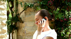 Woman sitting in the park and talking on cellphone Stock Footage