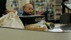 Mother and baby at grocery store check-out Stock Footage