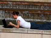 Stock Video Footage of Woman with laptop lying near the fountain
