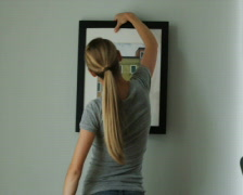 Woman deciding which picture to hang on the wall Stock Footage