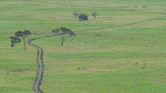 A safari jeep travels on a distant road in Africa. Stock Footage