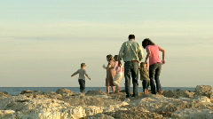 Family walking on rocks at the beach Stock Footage