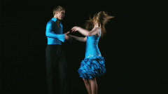 Young couple dancing the salsa against a black background Stock Footage