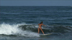 Woman catching a wave on a surfboard Stock Footage