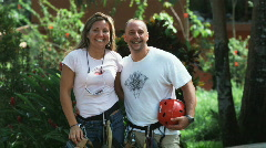 Couple wearing harnesses about to go on a zip line tour through the Costa Rican Stock Footage