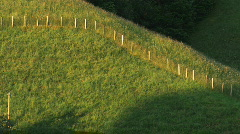 Grassy hill with a fence on it Stock Footage