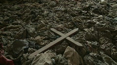 A cross sits amongst the scattered clothing of victims following a genocide in a Stock Footage