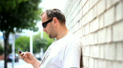 Man in sunglasses sending text message / sms Stock Footage
