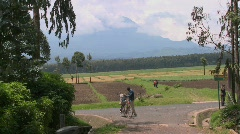 A man walks his bicycle down a rural road in Rwanda with the Virunga volcanos in - stock footage