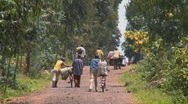 Stock Video Footage of People walk their bicycles loaded with goods down a rural road in Rwanda.