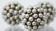 Stock Video Footage of figures consisting of metallic balls rotate around its axis