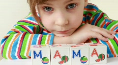 Girl has puted together cubes with letters for obtaining word Mama Stock Footage