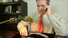Jeweler talking on phone with gun Stock Footage