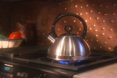 Teak kettle on stove Stock Footage