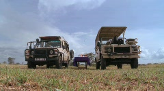 Safari jeeps are parked on the plains of Africa. Stock Footage