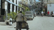 Stock Video Footage of A man pushes a handcart up a narrow boulevard in Stone Town, Zanzibar.