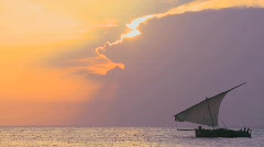 A beautiful sunset shot of dhow sail boat sailing off the coast of Zanzibar. - stock footage