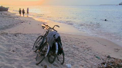 Sunset shot along a beach with two bicycles parked on the shore and children - stock footage
