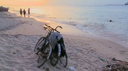 Stock Video Footage of Sunset shot along a beach with two bicycles parked on the shore and children