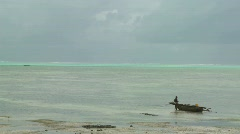 A distant native stands beside his dugout canoe in a tropical island paradise. Stock Footage