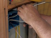 Electrician separating wires while wiring new wall box Stock Footage