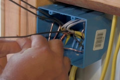 Electrician wiring an wall outlet box Stock Footage