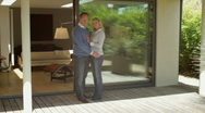 Stock Video Footage of Wide, Track shot portrait couple standing in front of house
