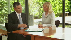 Wide, shot off female signing contract at dinning table and handshake financi Stock Footage