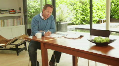 Wide shot of male at dinning table looking at personal finance - stock footage
