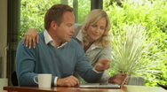 Medium shot of male and female at dinning table with laptop shopping online Stock Footage