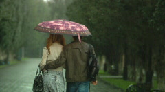 Girl and boy go under the umbrella Stock Footage