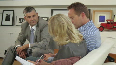Wide tracking shot off couple signing contractand handshake financial advisor Stock Footage