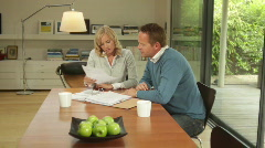 Wide shot of male and female at dinning table looking at personal finance - stock footage