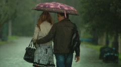 Man and a woman are walking under an umbrella in the rain in autumn Stock Footage